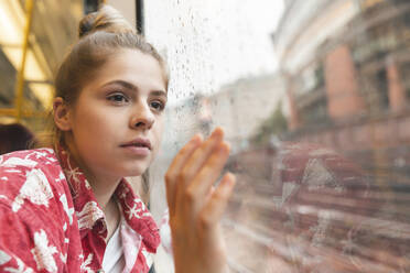 Young woman travelling by train and looking out of the window - WPEF01639