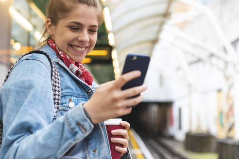 Happy young woman at subway station using a smartphone - WPEF01642