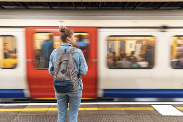 Rear view of young woman at subway station with incoming train - WPEF01645