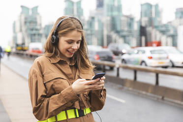 Happy young woman with headphones and cell phone in the city, London, UK - WPEF01651