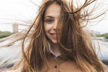 Portrait of smiling young woman with windswept hair, London, UK - WPEF01654