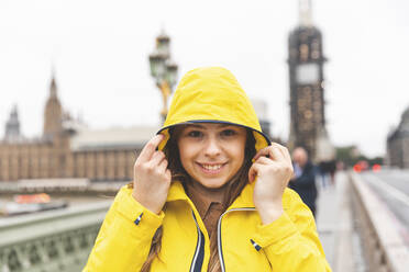 Portrait of smiling young woman wearing yellow raincoat on a rainy day, London, UK - WPEF01657