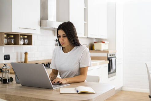 Young woman using laptop at home - GIOF06924