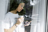 Young woman with cup of coffee and cell phone behind windowpane - GIOF06945
