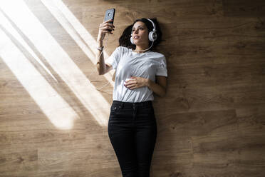 Young woman lying on the floor with smartphone and headphones - GIOF06960