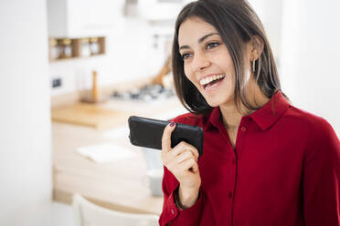 Happy young businesswoman using smartphone at home - GIOF06972