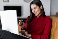 Happy young woman at home shopping online - GIOF06984