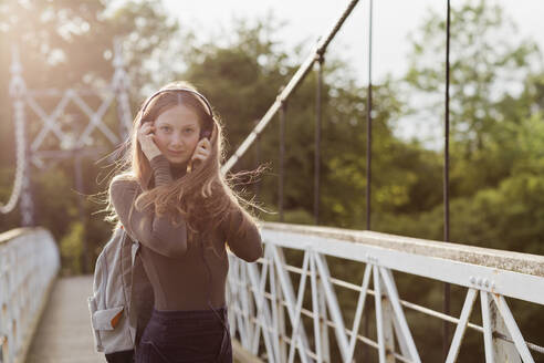 Teenage girl using smartphone and listening music on a bridge - NMS00370