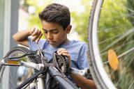 Deutschland, München, Junge 10 Jahre repariert Fahrrad - DIGF07721