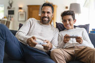Happy father and son playing video game on couch in living room - DIGF07724
