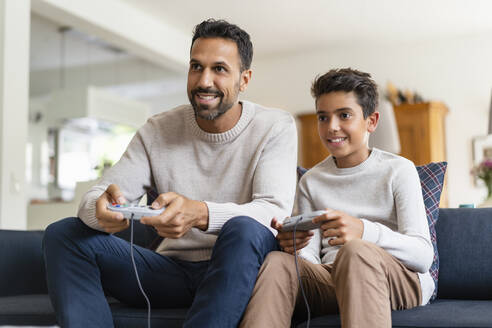 Happy father and son playing video game on couch in living room - DIGF07727