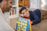 Father and son lying on the floor at home playing a game - DIGF07736