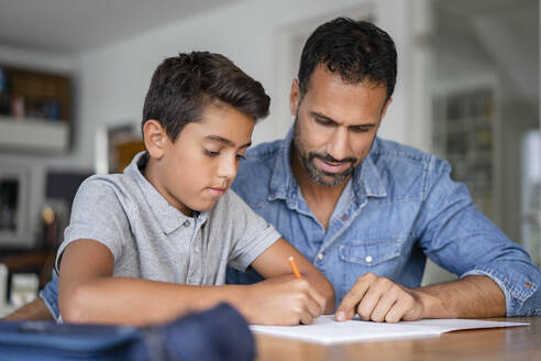 Father helping son doing homework - DIGF07745