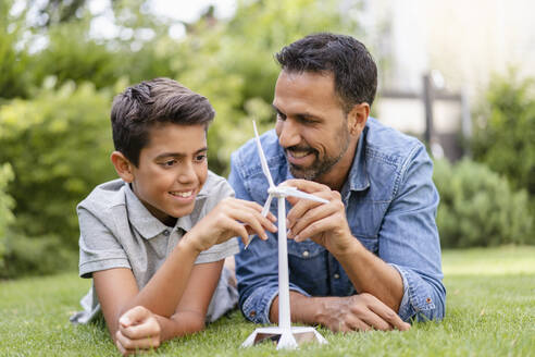 Smiling father and son lying in garden with a wind turbine model - DIGF07748