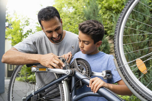 Father and son repairing bicycle together - DIGF07757