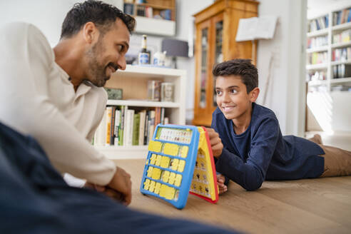 Father and son lying on the floor at home playing a game - DIGF07766