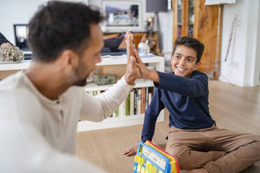 Father and son sitting on the floor at home playing a game and high fiving - DIGF07769