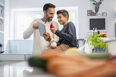 Father and son using tablet and cooking in kitchen at home together - DIGF07772