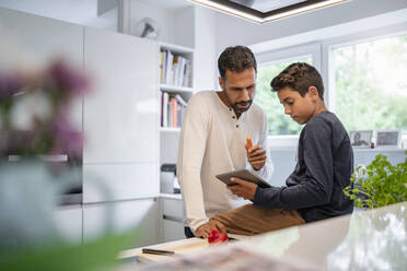 Father and son using tablet and cooking in kitchen at home together - DIGF07775