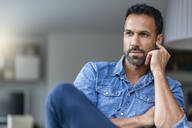 Portrait of a man wearing denim shirt at home - DIGF07781