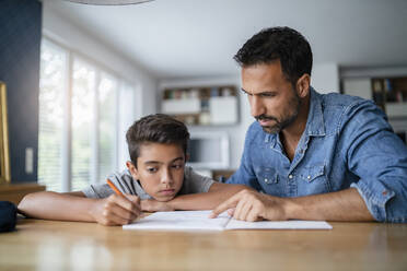 Father helping son doing homework - DIGF07784