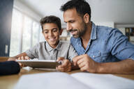 Father and son using tablet and doing homework - DIGF07787