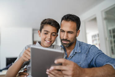 Father and son using tablet together at home - DIGF07790