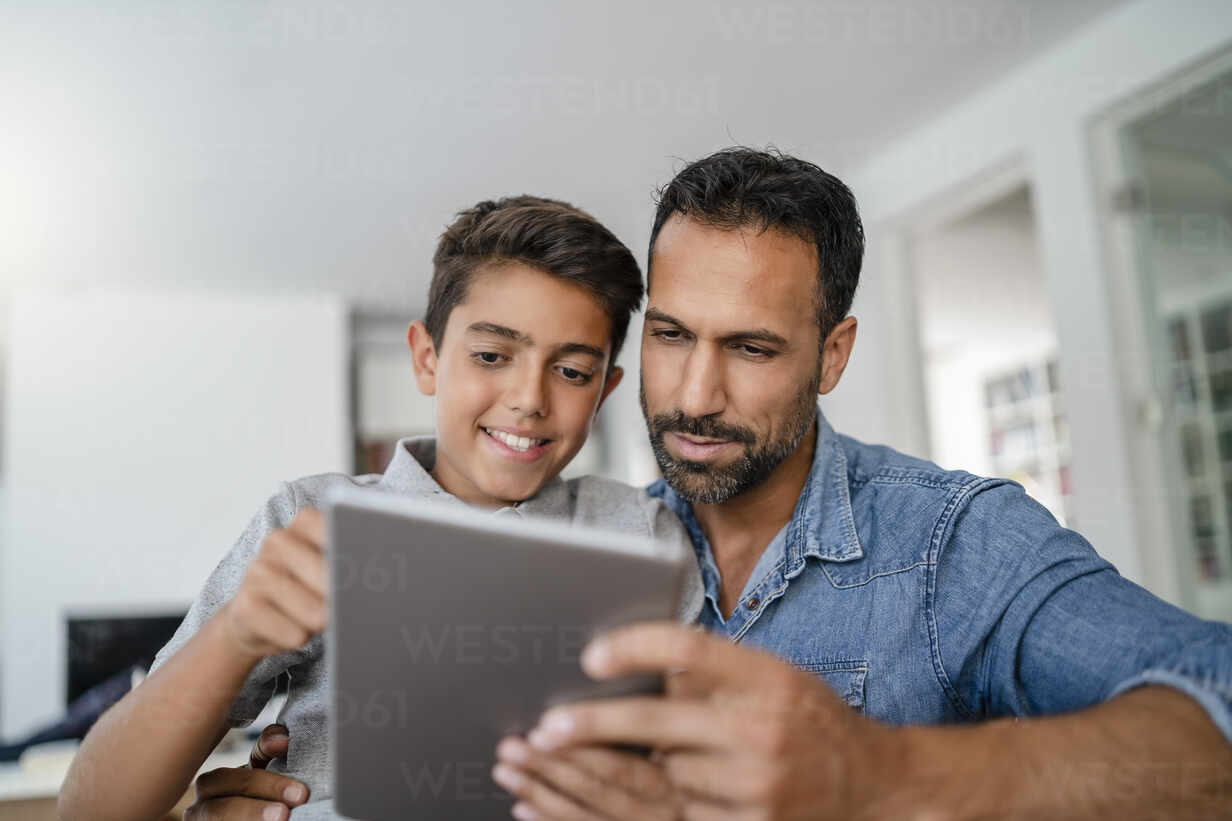 Father and son using tablet together at home - DIGF07790 - Daniel Ingold/Westend61