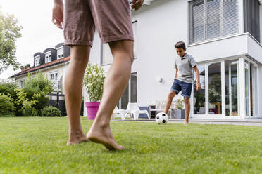 Father and son playing football in garden - DIGF07793