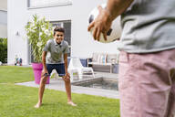 Father and son playing football in garden - DIGF07796