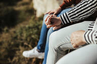 Close-up of gay couple holding hands outdoors - LJF00485