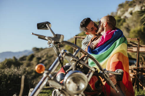 Gay couple with gay pride flag kissing on a motorbike - LJF00491