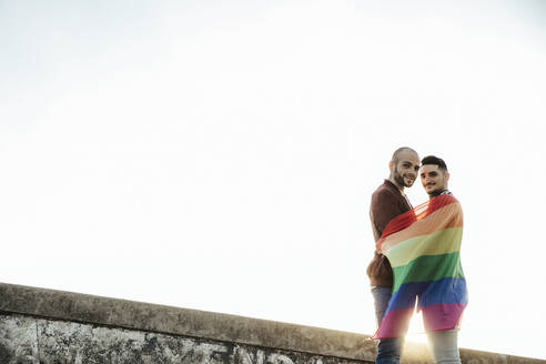 Portait of smiling gay couple with gay pride flag - LJF00500