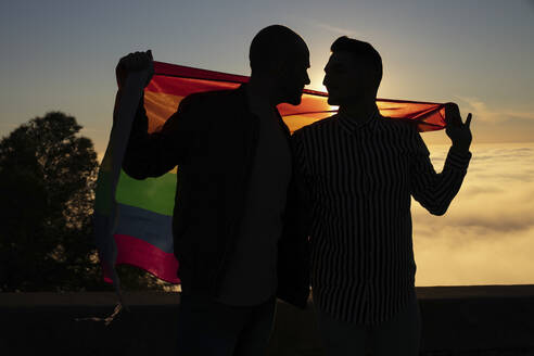 Silhouette of gay couple with gay pride flag in backlight - LJF00503