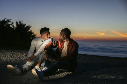 Gay couple sitting in the mountains above the clouds at sunset - LJF00515