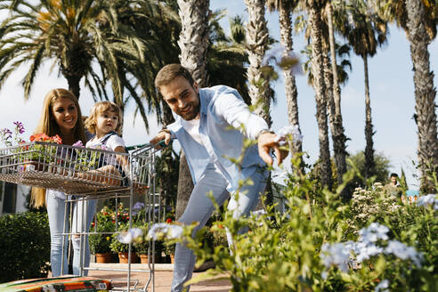 Happy family buying plants in a garden center wth the daughter in shopping cart - JRFF03459