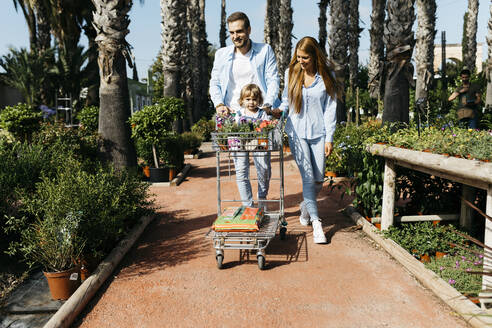 Family buying plants in a garden center wth the daughter in shopping cart - JRFF03462