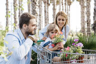 Family buying plants in a garden center wth the daughter in shopping cart smelling at a flower - JRFF03468
