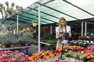 Female worker in a garden center using a tablet - JRFF03504
