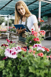 Female worker in a garden center with a tablet caring for flowers - JRFF03513