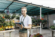 Portrait of a smiling worker in a garden center using a tablet - JRFF03516