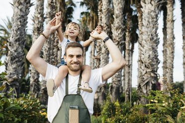 Portrait of a happy worker of a garden center with a girl on his shoulders - JRFF03528