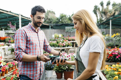 Customer paying with smartphone in a garden center - JRFF03540