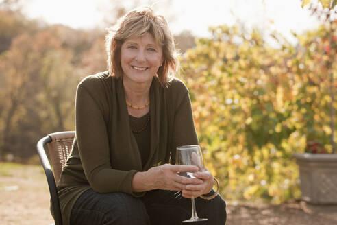 Caucasian woman drinking wine outdoors - BLEF12309