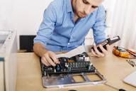Technician repairing a desktop computer - JRFF03555