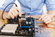 Close-up of technician repairing a desktop computer, soldering a component with tin - JRFF03561