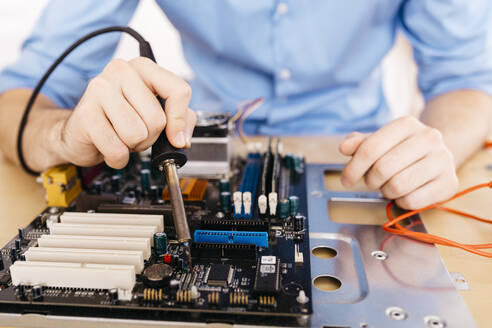 Hands of a worker repairing a desktop computer, soldering a component with tin - JRFF03561