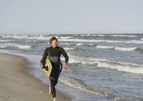 Surfer running at the beach - AHSF00714
