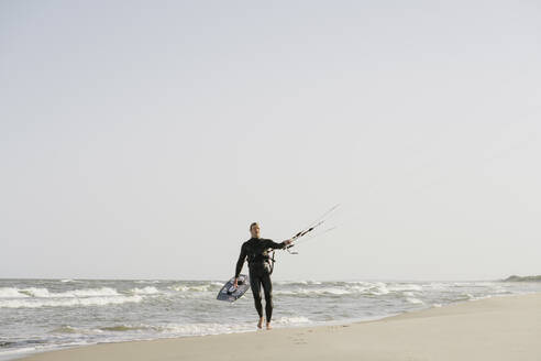 Kiteboarder walking with his kite at the beach - AHSF00717
