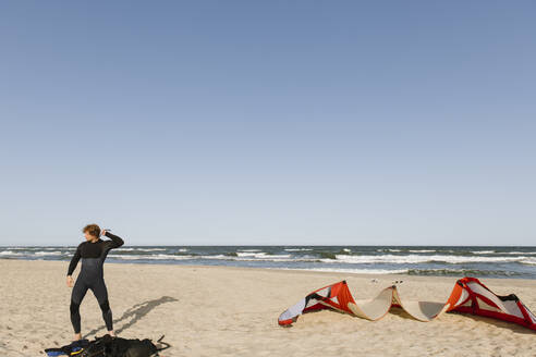Lithuania, Nida, A surfer puts on a wetsuit vest - AHSF00720